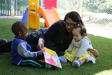 A teacher and two infants look at a book outdoors